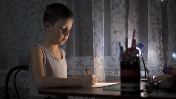 Little boy writing and drawing. Doing homeworks. Child. Adorable boy.