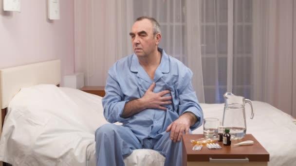 Kranker älterer Mann sitzt auf Bett und wählt Medikamente und Pillen.
