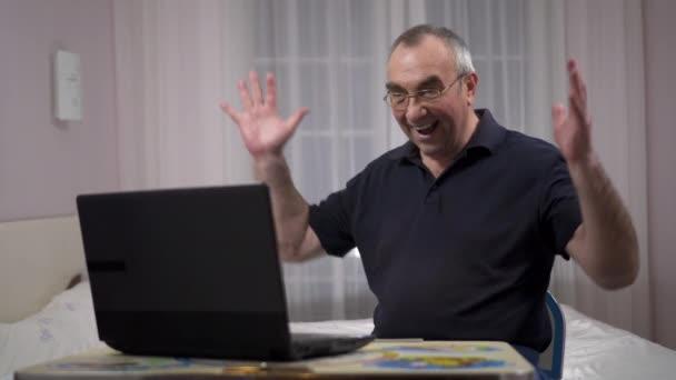 Ältere grauhaarige Männchen mit Laptop, Fußball auf einem Laptop zu beobachten und sich zu freuen