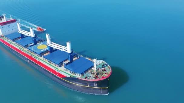 Letecký pohled: létání nad mohutnou lodí naplněnou pohybujícím se v tichém moři. Náklad přesunutý velkou mezinárodní nákladní lodí do konečného místa určení.