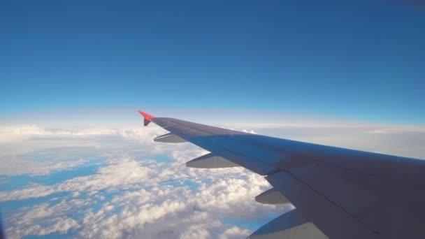 Flugzeugflug. Flügel eines Flugzeugs, das über den Wolken fliegt. Blick aus dem Flugzeugfenster. Flugzeuge. Flugreisen. 4K-UHD-Video