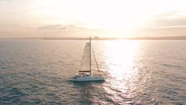 Letecký pohled. Katamaran pluje po moři, kamera se přibližuje a letí nad lodí, na západ slunce, krásný výhled