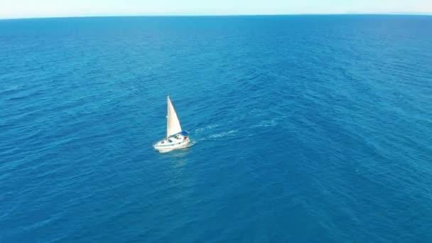 Jachta plachtí na otevřeném moři. Plachetní člun. Jachta byla viděna z dronu. Jachting, letecká 4k.