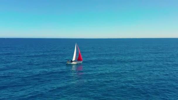 Jachta pluje na otevřeném moři za slunečného dne. Plachetnice s červenou plachtou.