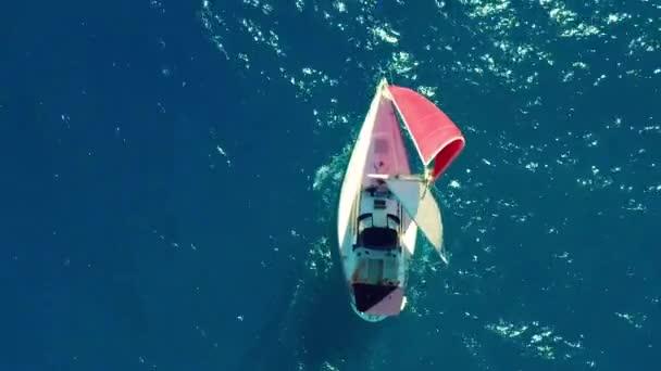 Légifelvétel. Gyönyörű vitorlás jachton, piros vitorlával vitorlázik a Smaragdparton, napsütéses napon.