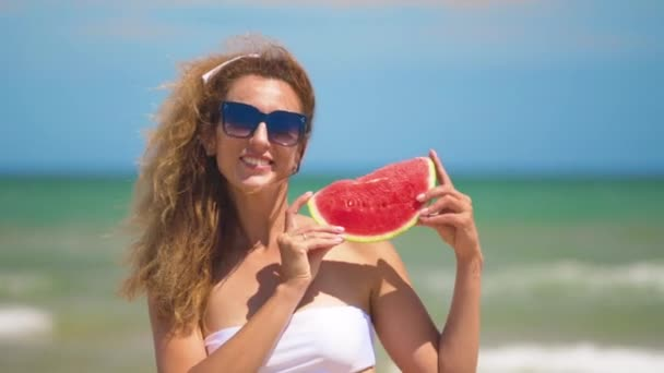 Smiling woman eating watermelon on beach. Woman eating tasty summer fruit. Happy summer time.