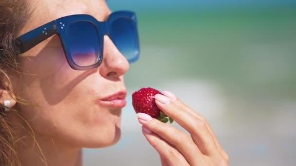Frau isst Erdbeeren in Meeresnähe an einem sonnigen Sommertag. Nahaufnahme.