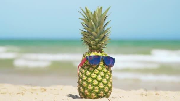Veselý ananas v slunečních brýlích na dovolené na moři. Koncept letní dovolené.