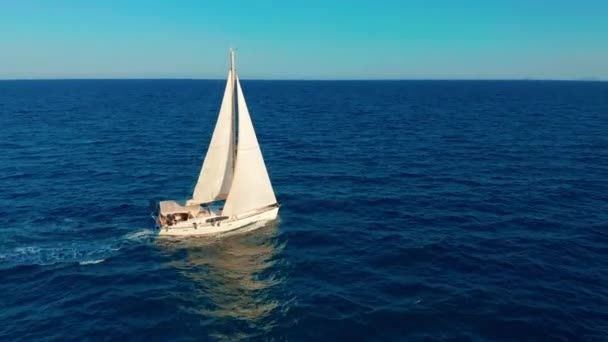 Plachetnice v oceánu. Bílá plachetní jachta uprostřed bezmezního oceánu. Letecký pohled.