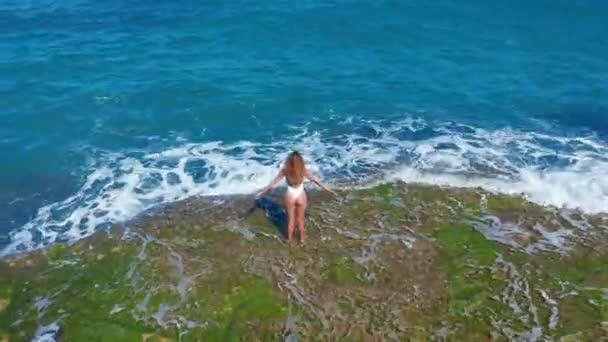 Légifelvétel. Szexi lány állt a szikla a Rocky Beach. Egy nő néz a távolba.