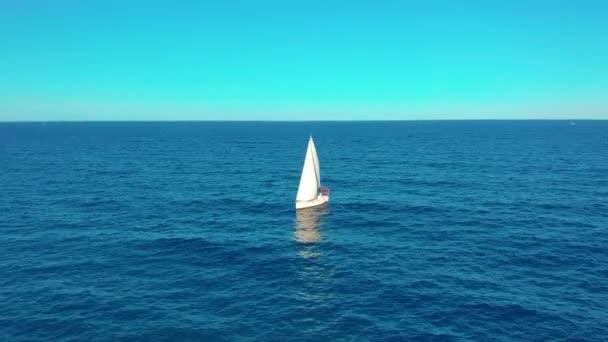 Letecký pohled. Jachta plachtí na otevřeném moři. Jachting s plachtami nahoře za větrného dne.