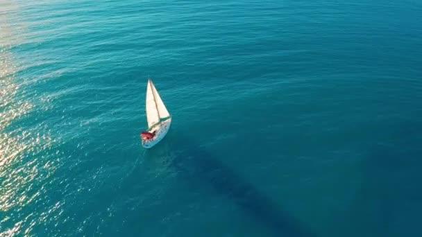 Letecký pohled. Jachta plachtí na otevřeném moři. Plachetní člun. Jachta shora. Jachting za větrného dne. Na jachtě. Plachetnice.