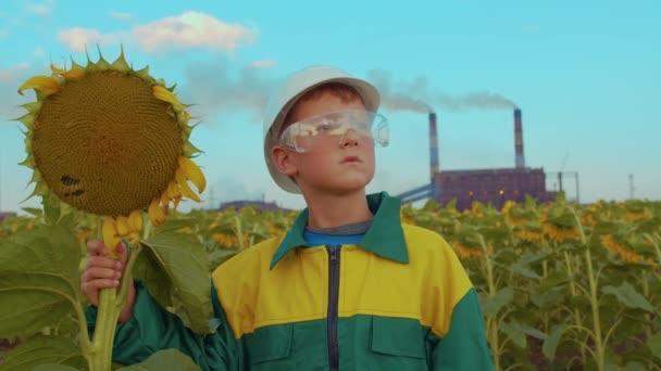 Kind in Schutzmaske mit der Pflanze Sonnenblume auf dem Hintergrund Industrieanlage. Umweltverschmutzung, ökologische Katastrophe. Sorge für zukünftige Generationen.