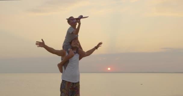 Šťastný otec a syn si hrají s hračkou společně při západu slunce šťastná rodina chůze venku.
