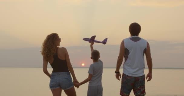 Šťastná rodina. Chlapec se svým otcem a matkou při západu slunce.
