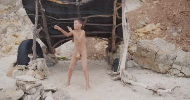 Höhlenmensch, männlicher Junge, der tanzt. lustige junge primitive Junge im Freien. Urzeit-Stammesmensch draußen auf wilder Natur.