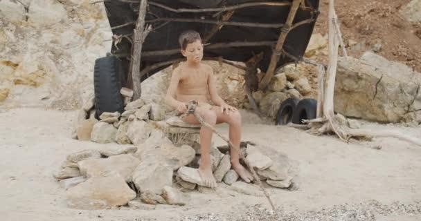 Höhlenmensch, männlicher Junge. lustige junge primitive Junge im Freien. Evolution Survival Konzept. Ein ruhiger Junge sitzt draußen in seiner felsigen Siedlung. Urmensch.