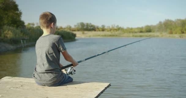 A kisfiú a riveren halászott a régi mólón.