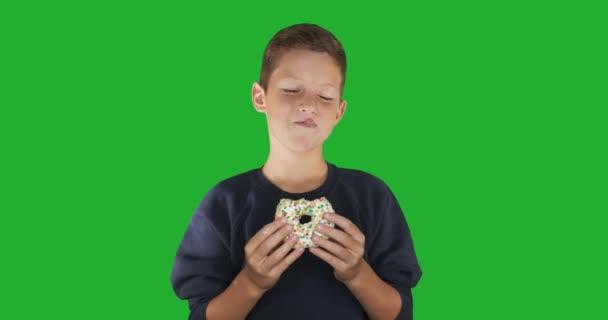 Közelkép. Egy vicces fickó arcképe, amint színes fánkot eszik. Kifejezések, diéta koncepció, háttérszín. 4k.