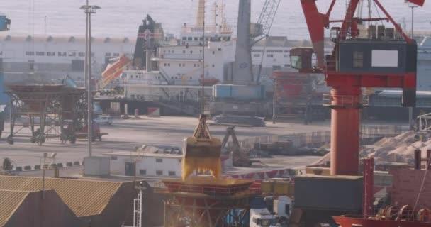 Casablanca, Marokkó - 2019. október 15.: Grapple crane loading. Kereskedelem, tengerészet. Mezőgazdasági rakomány szállítása vízi- és teherautóval. Daru kirakodás és berakodás a kikötőben.