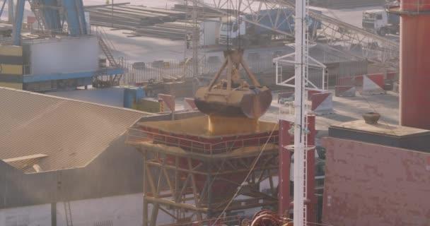 Csákány daru betöltése. Kereskedelem, tengerészet. Mezőgazdasági rakomány szállítása vízi- és teherautóval. Daru kirakodás és berakodás a kikötőben.