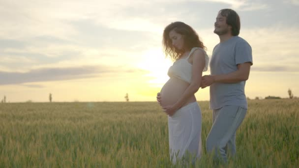 Pregnant couple of husband and wife feels love and relax at home. Young expecting woman holds baby in pregnant belly. Father take care of pregnant mother. Concept of maternity and pregnancy care.
