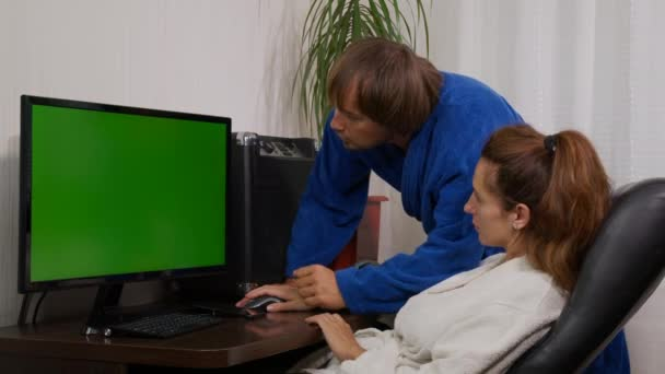 Businessman and businesswoman in home clothes at home with green screen chroma key PC on the table.