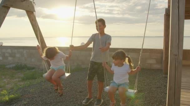 Děti různého věku a pohlaví na houpačce. koncept šťastného dětství.