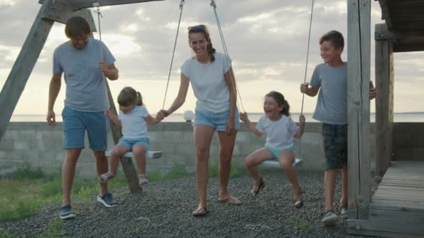 Happy family on a swing at sun light. Happy family concept.