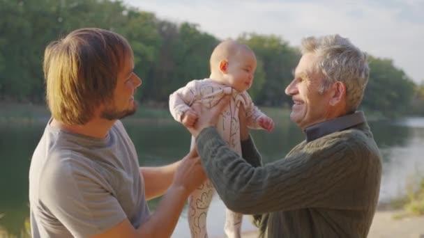 Großvater mit Säugling im Arm draußen. Bindung der Großeltern an das Enkelkind.
