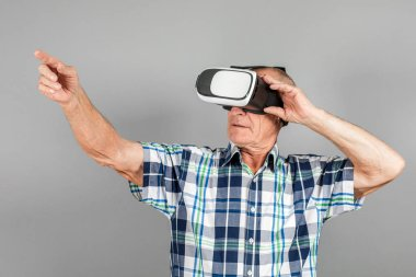 Grandfather looks into VR glasses, hand gestures, on a gray background