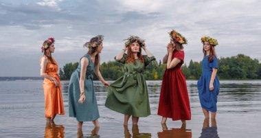 Doğada çiçek çelenkleri içinde güzel kızlar. Antik putperest kökenli kutlama konsepti. Yaz gündönümü günü. Yaz ortası.