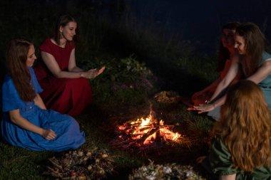 Geceleri şöminenin yanında güzel kızlar. Antik putperest kökenli kutlama konsepti. Ivan Kupala 'nın Gecesi.