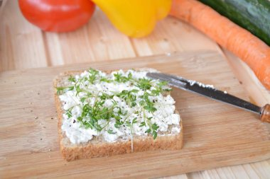 A wholemeal toast with coarse-grained cream cheese and cress lies on a wooden board with a knife next to it and vegetables such as paprika and tomato, as well as cress, cucumber and carrot on a table
