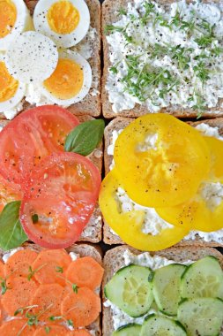 Many whole-grain toasts with different toppings lie on a dark surface - concept for healthy nutrition with vegetables on a wholemeal toast and coarse-grained cream cheese as background