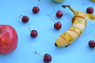 Different types of fruit, such as apples, cherries and bananas lie on a single-footed base and are wrapped in a measuring tape - concept for healthy weight loss that makes fun