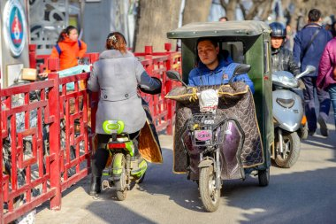 BEIJING, CHINA - MARCH 10, 2016: People are driving through the streets with bicycles, scooters and cars.