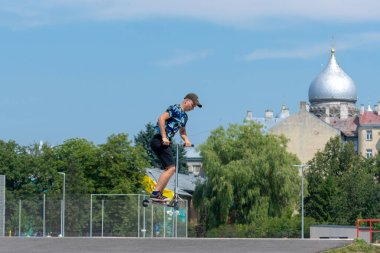 RIGA, LATVIA - JULY 20, 2018: The teenage in the skatepark carries out various tricks with scooters.