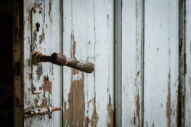 Selective focus photography. Old wooden door with damaged paint.
