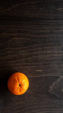 Healthy orange fruit and copy space. Ripe organic orange on black wooden surface with text space.