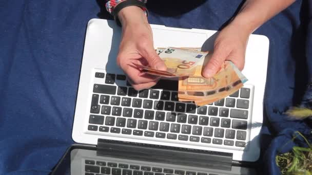 hands counting banknotes on a laptop