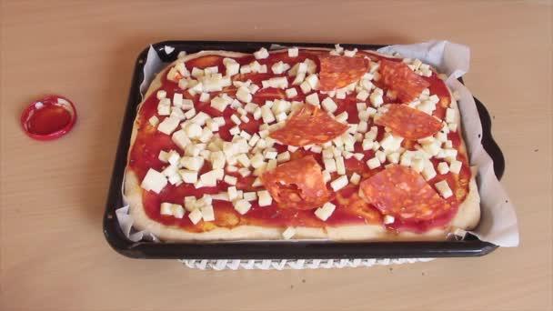 pikantní salám nakrájený na proužky padající na italskou pizzu z kysaného těsta