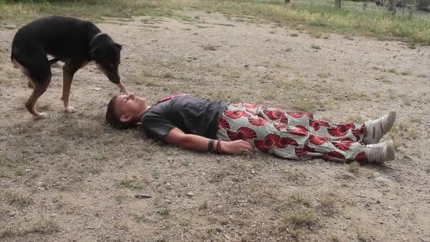 schwarzer Mischlingshund, der der Herrin, die sich beim Herzinfarkt schlecht fühlt, hilft, indem er ihr die Ruhe gibt, indem er ihr Gesicht leckt und dann rennt, um Hilfe zu suchen