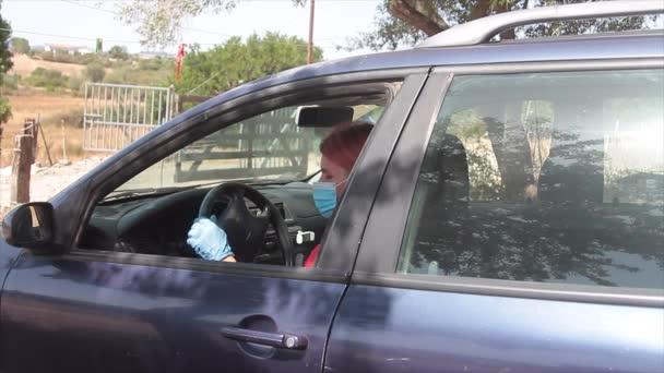 női pizzafutár, aki két karton olasz pizzát szállít közvetlenül az ügyfél otthonába, és egészségügyi maszkkal a száján száll ki a kocsiból, hogy megelőzze a covid19 vírust.