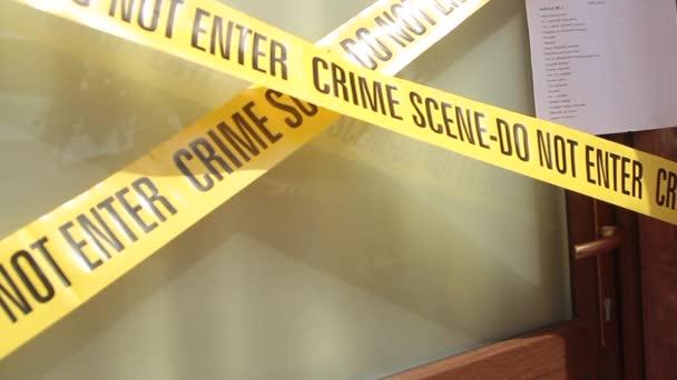 Tür eines Hauses mit Tatortklebeband und dem Papier, das es der gerichtlichen Beschlagnahme unterzieht, die gewaltsam durch die Hand eines Detektivs mit blauem Handschuh abgeschafft wird