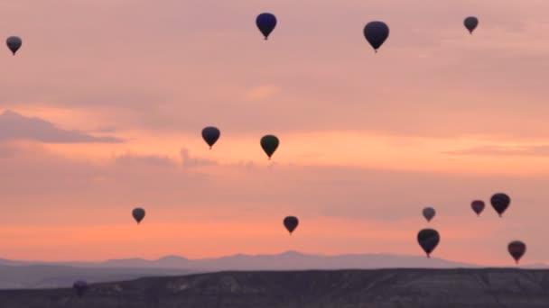 Silhouetten viele Heißluftballons fliegen über Täler in Goreme, Türkei. rosa Morgenröte über dem unglaublichen Ort in den türkischen Bergen.