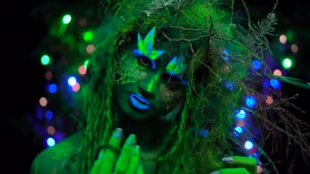 Aranyos misztikus zöld Driád Uv fluoreszkáló fekete fény mosolyogva és jelentenek az izzó fa háttér