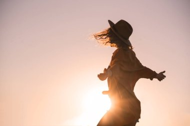 Curly chestnut-haired sexy girl in jeans shorts and hat is spinning and have fun at sunset