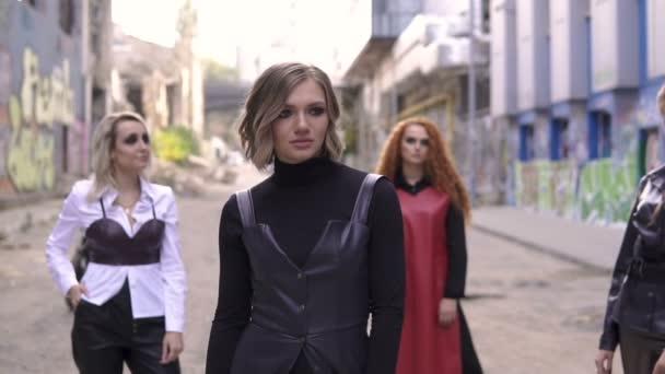 Čtyři dívky podivné módní kožené a černý motocykl. Mladé sexy punková ženy v městské graffiti scéně. Zpomalený pohyb