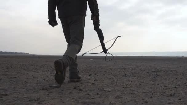 Gyalogos zombi veszélyes szörnyeteg nehéz kereszt íj a sivatagban. Horror karakter fogalma, a fegyveres és a grasepainted egység